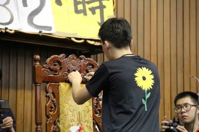 ▲王金平立法院長の椅子からガムテープあとを丁寧に剥がす学生