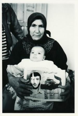 ▲殺された息子の死亡証明書と遺された孫を抱く祖母――2001年1月、ガザ