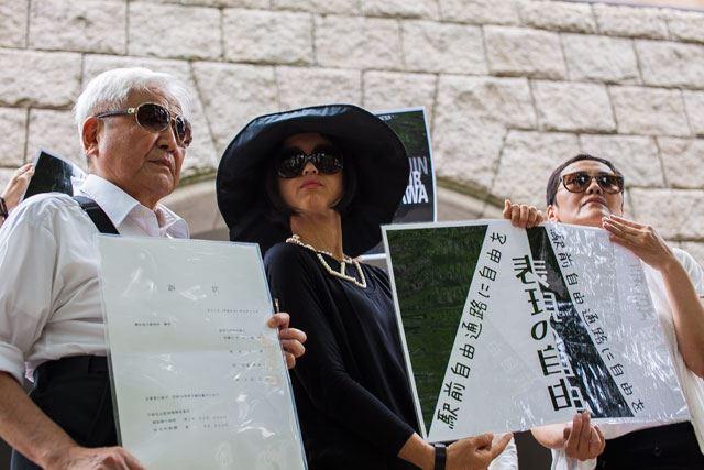 ▲訴訟代理人の大川弁護士(左)も「マネキンフラッシュモブ」に参加、「訴状」と書かれたプラカードを掲げた