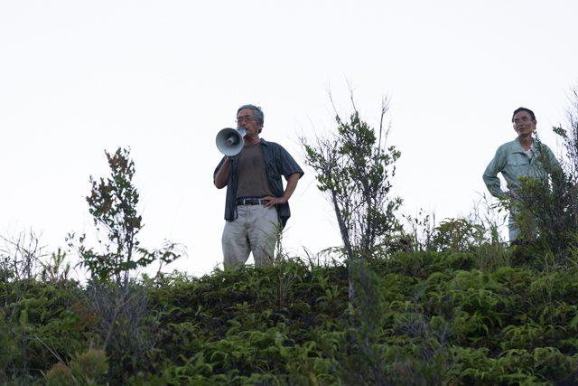 ▲AM6:17 崖の上から北側の状況を南側の市民に説明する沖縄平和市民連絡会の北上田毅氏。