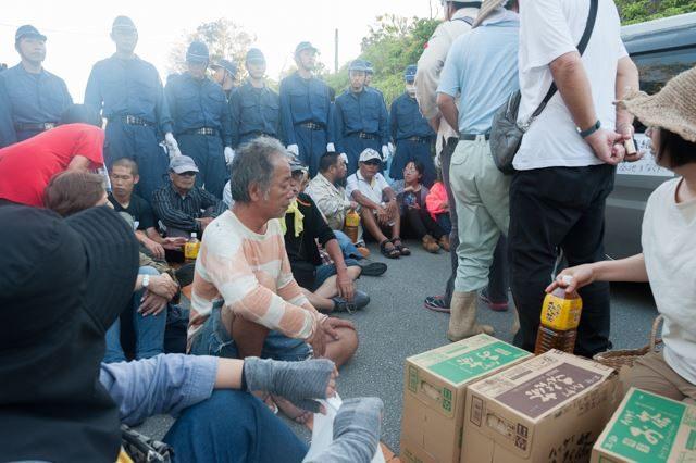 ▲AM6:49 壁になった機動隊の足元に座り込む。お茶などの物資が現場で共有された。