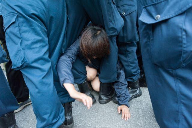 ▲AM6:56 車の周りに座り込んでいた女性。機動隊から逃れようとして阻まれる。