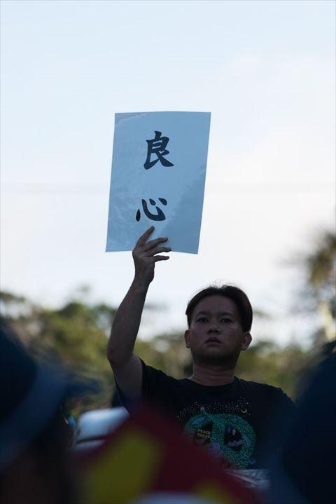 ▲AM7:00 「良心」と書かれたプラカードを掲げて訴えかける男性