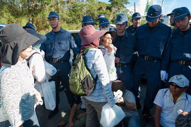 ▲AM7:55 N1ゲートへ続くたった一本の県道は、機動隊によって数キロ下で封鎖されている。高江で抵抗する市民たちに食料を届けたいと、車を乗り捨て、徒歩で坂道を2時間かけて登ってきた支援者の女性たち。機動隊に阻まれてゲート前のテントに近づけずにいる。