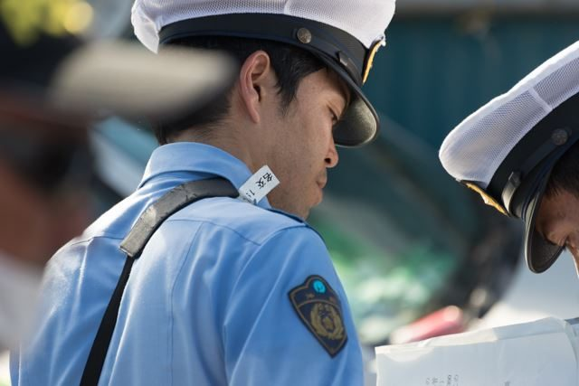 ▲AM9:23 10年間ゲート前を塞いでいた車を撤去するために、無理やり作られた口実が「駐車違反」。アリバイ作りのように交通課の警察官が現れた。