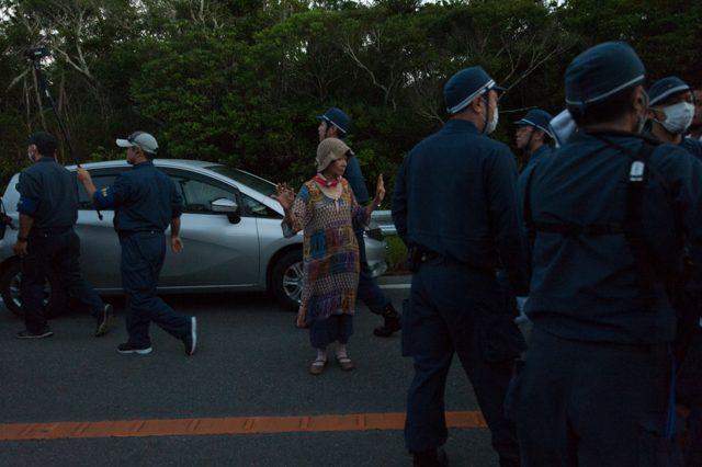 ▲ AM5:42 北側からゲート前に向け、次々になだれ込んでくる機動隊に対し、抵抗せずに抗議の意志を示す女性。