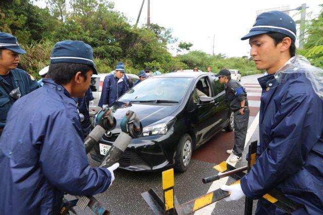 ▲ゆっくり車やバイクを走らせる市民に対し、早く進むよう呼びかける警官らは、市民らが従わなければレッカー移動に踏み切る
