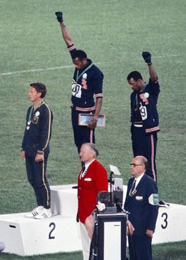 ▲表彰台上で米国の人種差別に抗議するピーター・ノーマン、トミー・スミス、ジョン・カーロス(左から)(写真はウィキメディアコモンズより転載)