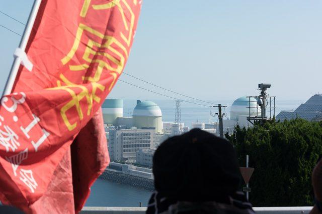 ▲抗議の市民たちが見つめる中、再稼働の朝を迎えた四国電力伊方原子力発電所