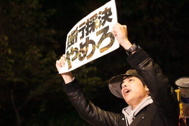 ▲国会に向かって「強行採決やめろ」のプラカードを掲げる若い男性