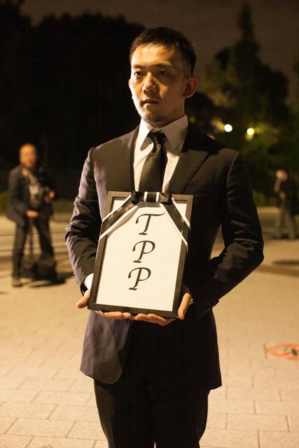 ▲喪服を着た男性。「遺影」を真似たと思われる額縁の中には「TPP」の文字