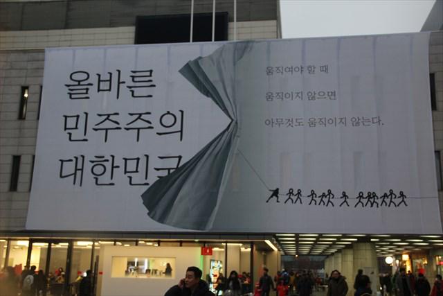 ▲光化門広場に隣接する世宗文化会館に掲げられた巨大な看板。メッセージは、左「正しい民主主義の大韓民国」右「動くべき時に、動かなければ、何事も動かない」