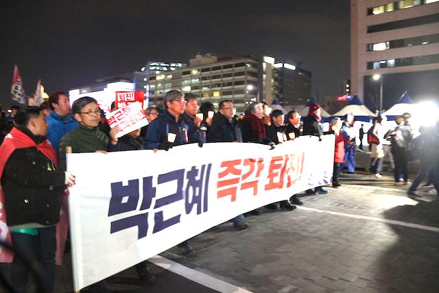 ▲「朴槿恵直ちに退陣」と書かれた横断幕をかかげ、青瓦台に向かって行進する労働者と学生たち。