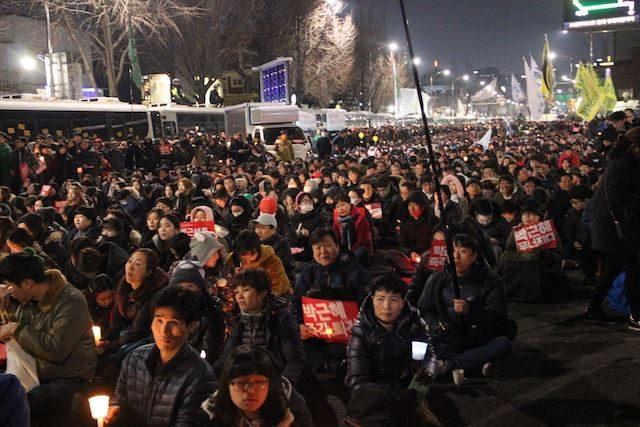 ▲ポリスライン付近に人々が座り込み、シュプレコールや、朴大統領を風刺した歌が大合唱される。