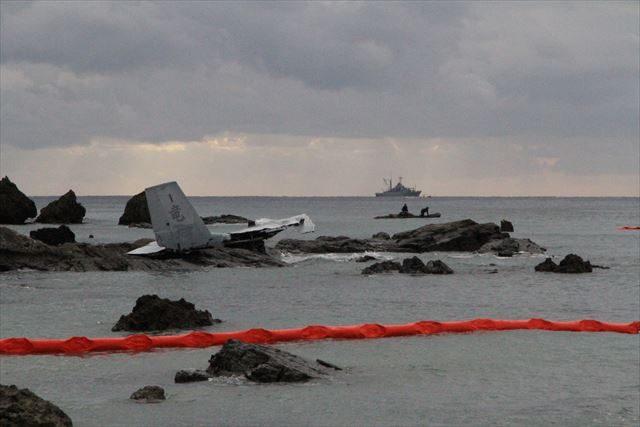 ▲メディア向けの規制線から撮影したオスプレイの残骸。「竜」と書かれた大きな尾翼が大破し、岩場に打ち上げられている。