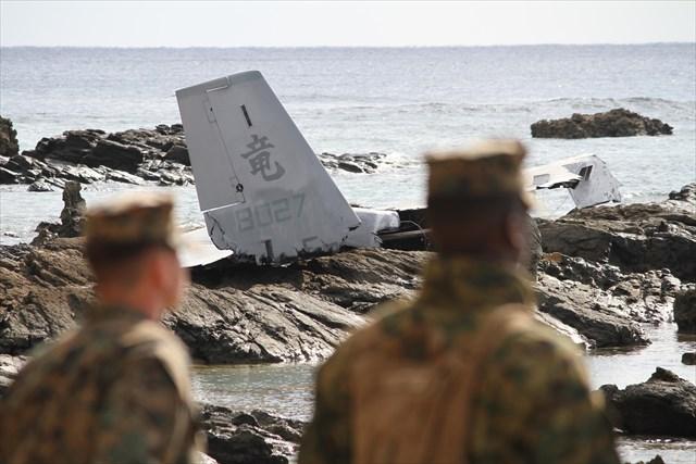 ▲報道陣が集まる北側からみえる風景。「竜」と書かれたオスプレイの尾翼の破片が、岩場の上に鎮座している。各社が紙面やテレビで報じている画角だ(前日14日にIWJ記者が撮影)。