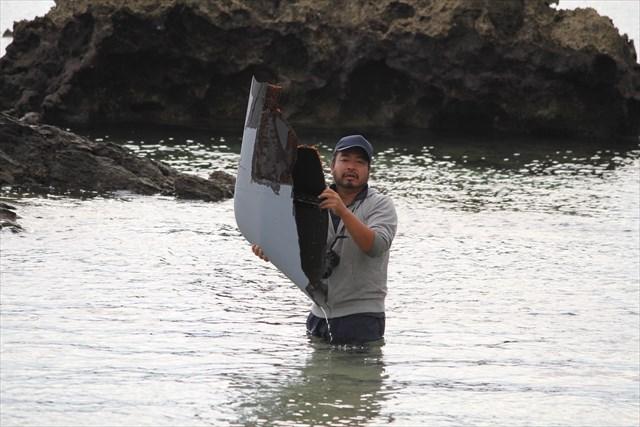 ▲海に浮かぶオスプレイの残骸を軽々持ち上げる大袈裟太郎氏。材質が軽いことが、よくおわかりいただけると思う。