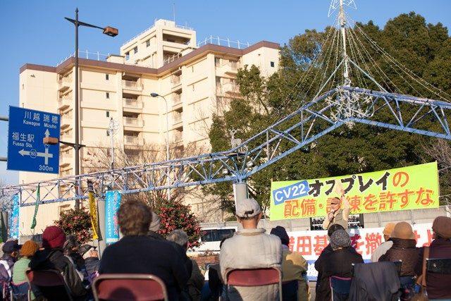 ▲12月18日に開催された「横田基地の撤去を求める座り込み行動」には、主催者発表によれば106名が参加した。集会が行われたフレンドシップパーク(東京・福生市)の車道を一本挟んだ塀の向こう側に、横田基地が広がる。写真の背景に写るビルと樹木は基地の敷地内のもの。