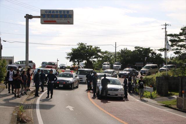 ▲高江で一般車両を停め、警察車両や工事関係車両だけを通行させる機動隊(2016年8月9日、IWJ記者撮影)