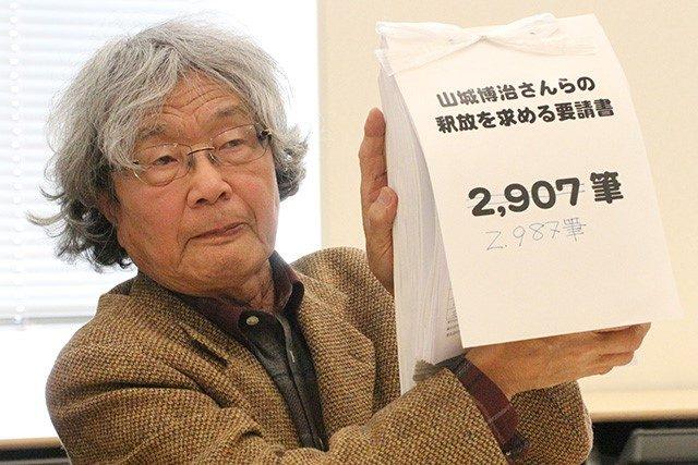 ▲インターネット以外で集まった署名の束(2987筆)を掲げる鎌田慧氏(ルポライター)