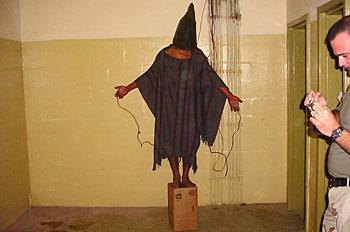 ▲アブグレイブ刑務所での米軍によるイラク人拘留者に対する虐待の様子。この人物は両手と性器にワイヤーをつけられ、箱から降りようとすると電気を流されたという(写真:Wikipedia)