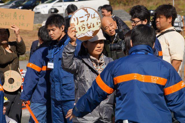 ▲起工式の会場入りをJR東海職員(青いジャケット)たちに阻まれても抗議を続ける住民。