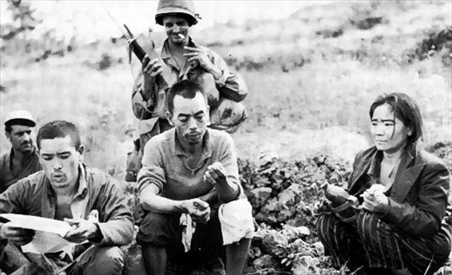 ▲降伏を促すビラを手に取る沖縄住民(ウィキペディアより)。